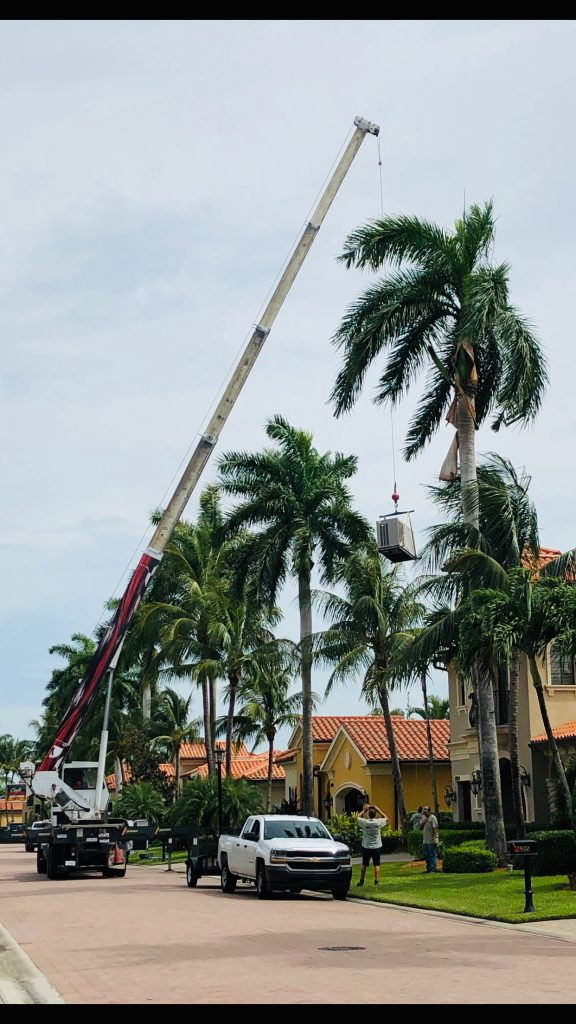 Tropical Generator employees installing a 38kW generator with a crane.  The generator weighs 1200 pounds and requires 3 people to install. Naples/Collier County.